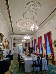 Long, rectangular interior room with a large table set for a meal. Portraits hang from the left wall, and red curtains hang from the windows on the right wall. White plasterwork ornaments the ceiling.