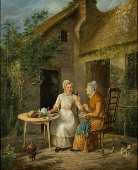 Two women seated at a round table just outside a small cottage talk to each other. Another woman watches from a darkened doorway behind them.