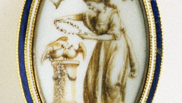 "An almond shaped brooch with an image of a woman laying a wreath on two doves. Above the woman, a floating banner says ""To Friendship."" The brooch has bands of white and blue enamel framing the image."