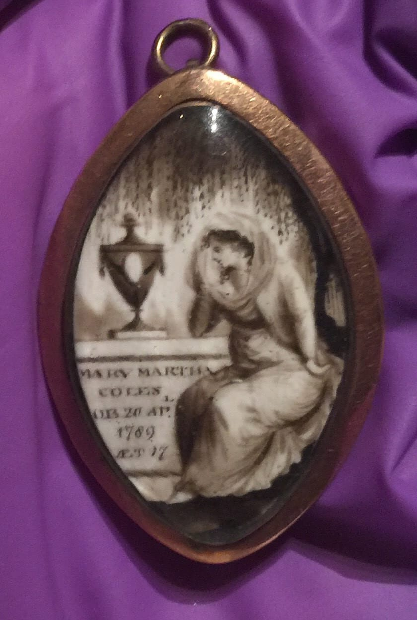 A pendant with a picture of a woman crying over a tomb with an urn on it.  The leaves of a weeping willow hang above her.  The tomb has an inscription with the name of the person who died and the date, 1789.