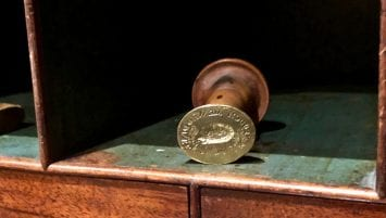 A brass seal with a wooden handle sits inside a tambour desk's pigeon hole. The face of the seal is oriented directly towards the viewer.