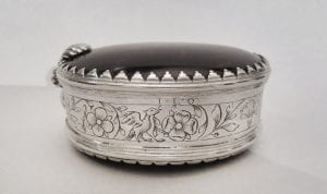 An oval silver and tortoiseshell box with engraved flowers.