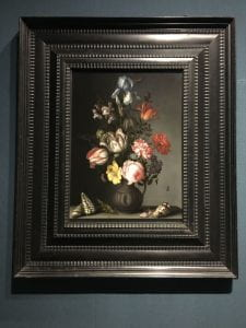 A painting with a vase of flowers that includes, among others, an iris, three broken tulips, a variegated carnation, snap dragons, a cabbage rose, and a fritillaria meleagris.  A grasshopper, petals, and three cone snail shells are on the table front of the vase.