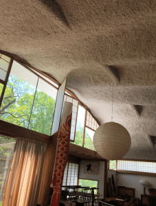 A photograph of the curved white cement ceiling in the Nakashima living room turned gallery