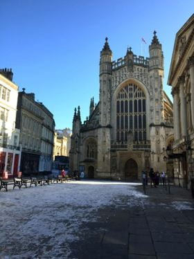 A cathedral, Bath Abbey, on a sunny morning. The street in front of it is covered with ice and snow.