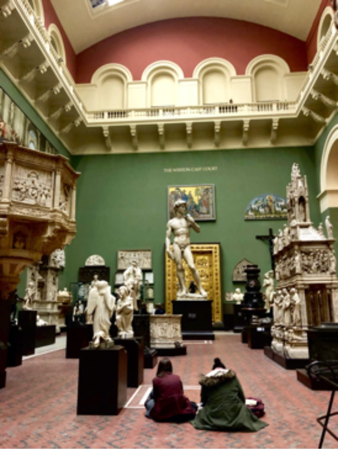 Alt Text: Two young women sitting crossed legged on the floor of museum gallery full of plaster casts of classical, medieval, and renaissance sculpture. They are sketching the plaster cast of Michelangelo's David.