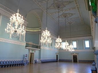 Five huge chandeliers hang in a large blue ballroom with extensive decoration on the ceiling.