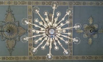 A chandelier seen from below. The branches form a star-like pattern. Behind, beige and coffee colored floral plasterwork can be seen against the blue of the ceiling.