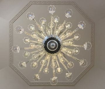 Another star-like pattern of a chandelier from below. The octagon molding on the ceiling can be seen behind it.