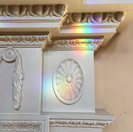 A fireplace molding with rainbow light refracted through a chandelier prism.