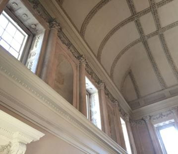 A corner of a room with Neoclassical decorative elements. The limestone of the columns and niches is a salmon-pink.