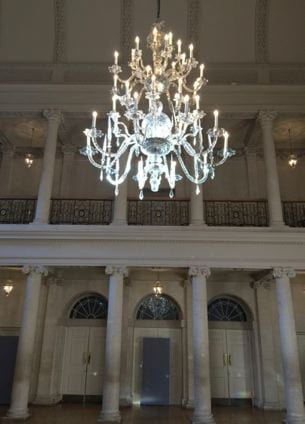 A chandelier with many branches hangs in a large room.  Behind it is a walkway set on top of a series of limestone columns.  On the ground floor are three doors.