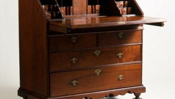 A slant-front desk with an open lid and chest of drawers beneath on five round feet.