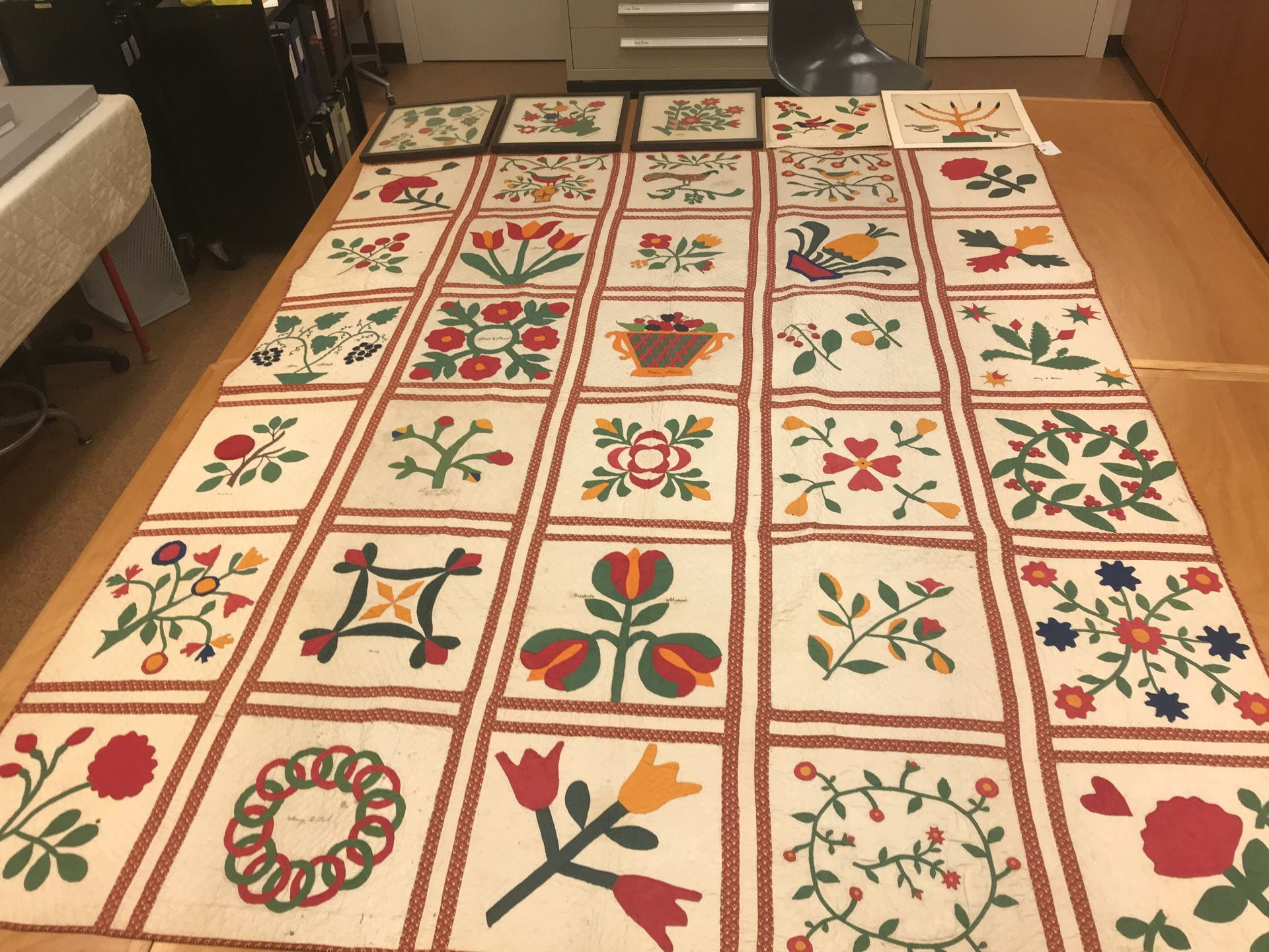 A row of separate, framed red and green quilt blocks line up neatly with the edge of a large red and green finished quilt.