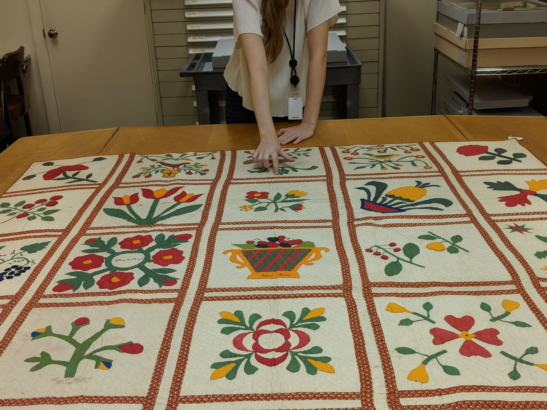 A woman points at a red and green quilt with various flowers, fruit, and geometric shapes on a table in the textile study lab of Winterthur.
