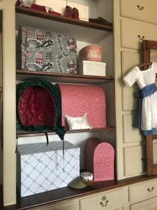 Bandboxes, caps, children's shoes, and a child's garment hang from drawers and sit on shelves in a shop display.
