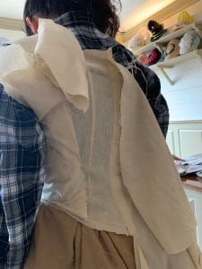 A woman stands with her back to the camera. Beige fabric has been pinned to hug the shape of her back.
