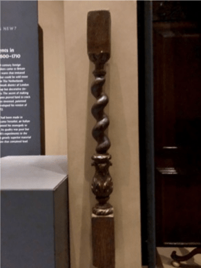 Alt Text: A dark-brown wood column and urn-style baluster with a twisted column on top of an urn decorated with carved acanthus. The baluster is not behind museum glass, but out in the open.