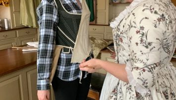 Two women stand in a mercantile shop. One is being fitted for a gown with beige fabric, and the other is pinning the fabric into place.