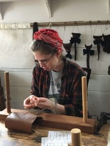 A woman is seated at a table. In front of her is a wig-maker's loom, which she works at with concentration.