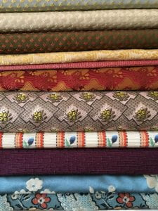 A photograph of 11 different fabrics. Each a different pattern and in a range of colors.
