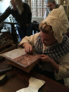 A woman in eighteenth-century costume works, seated, engraving a copper plate which is set on a pillow on a work surface in front of her.
