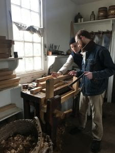 A man braces a piece of wood against a spike in a workbench while shaving it with a drawknife.