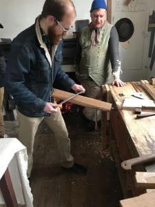 Two men stand behind a vise holding a piece of wood between two spikes.