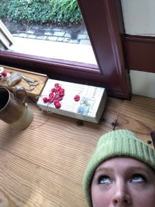The author takes a selfie while she is laying on a tailor's platform in front of an open window.