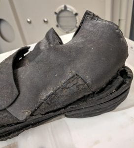 Photograph of the back three-quarters of a black leather shoe. The shoe appears dirty and worn. The sole of the shoe is cracking away from the upper leather portion. The center portion of the shoe appears to have been repaired.