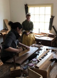 A woman uses a plane on a piece of wood in a workshop, while another woman in 18th-century garb looks on.