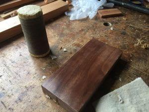 A polissoir and a rectangular piece of walnut.