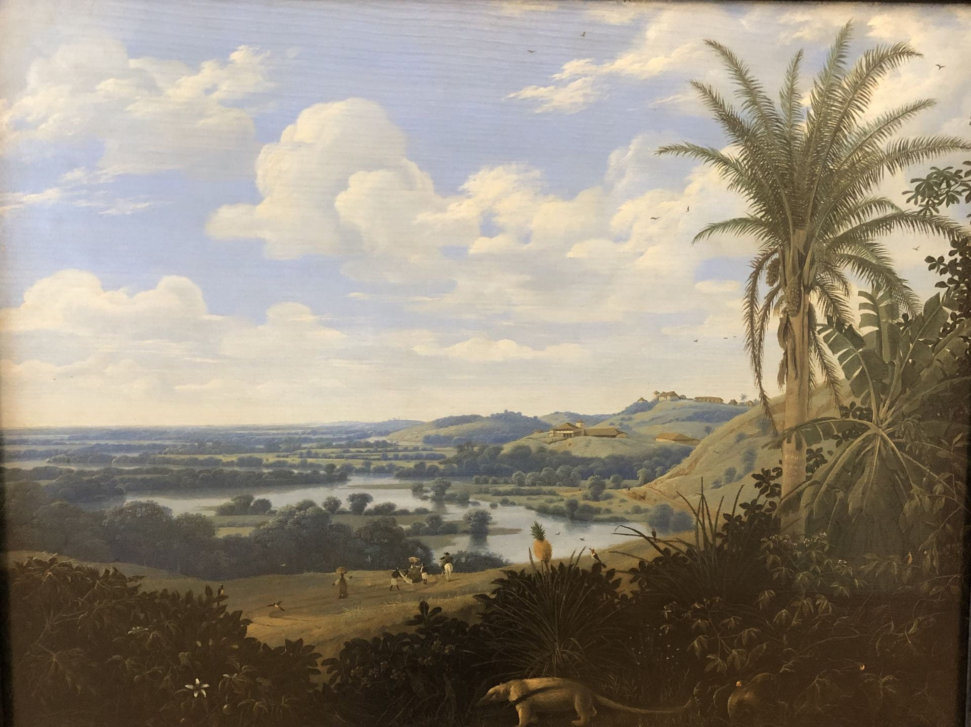 A landscape with large palm tree at right. An anteater walks through the foreground. The middle- and back-grounds are dominated by bands of golden pasture and darker forest, all below a large blue sky.
