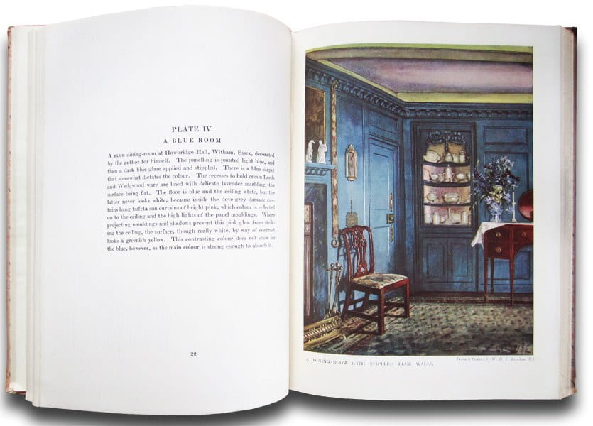 Book open to image of a dining room painted blue with a fireplace, chair, and buffet table.