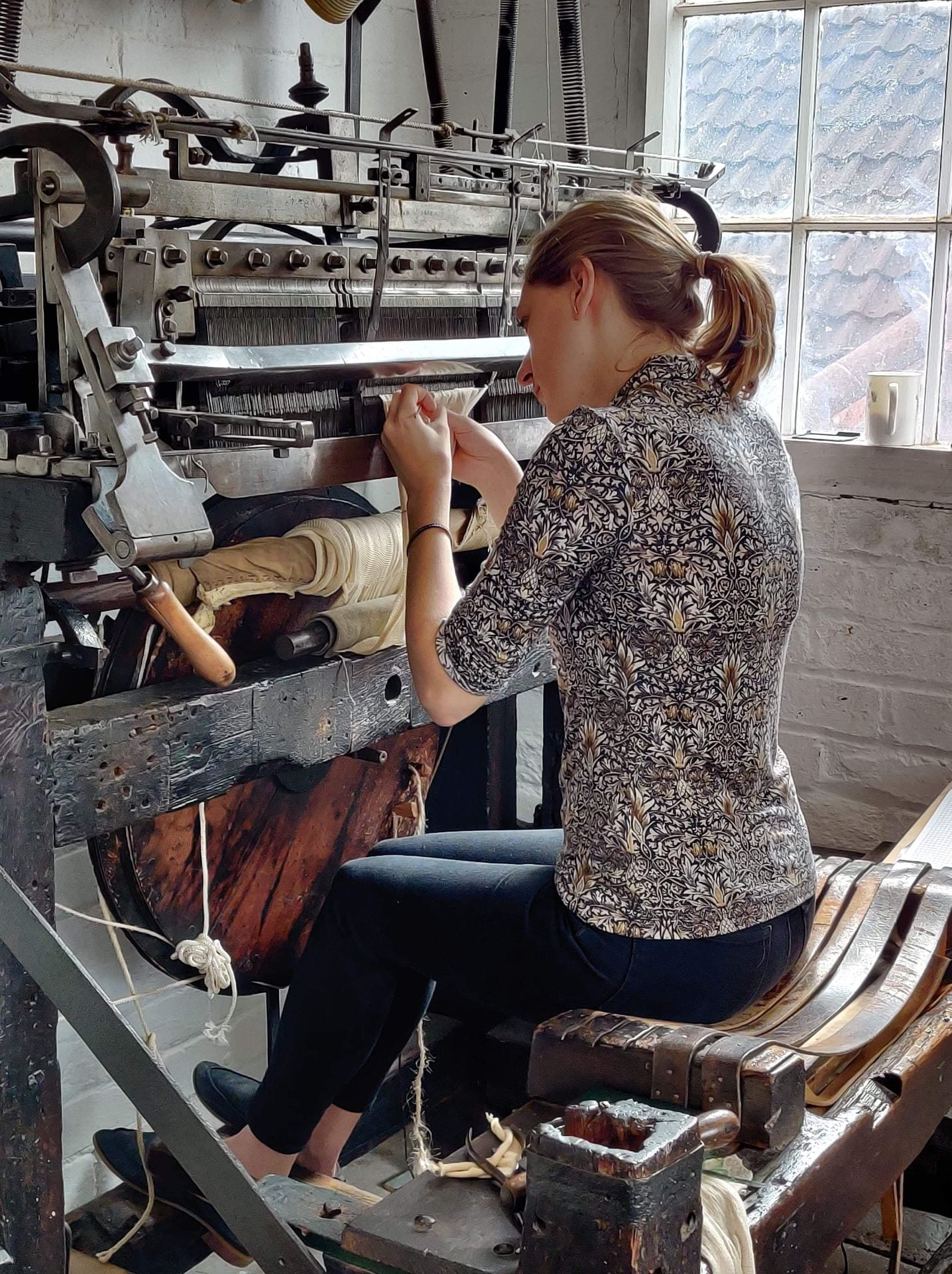 The author sits in front of a knitting machine with a piece of knitted fabric hanging from it, using a tiny hook to make a pattern.