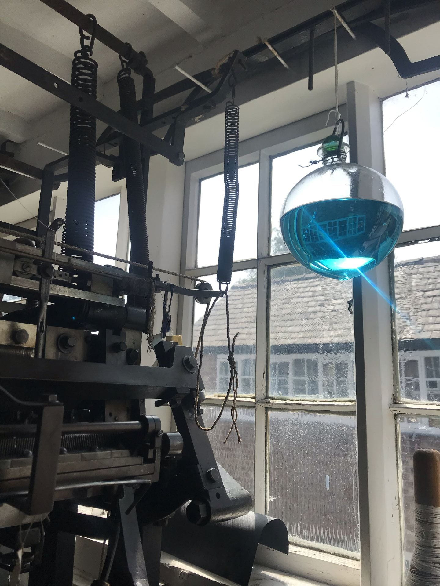 a large glass orb filled with blue water hangs over a knitting frame by a window.