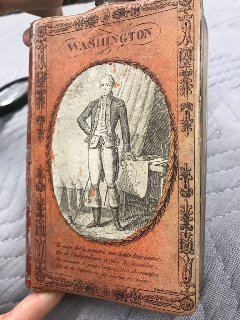 "Glass flask covered with orange paper featuring a print of George Washington, the title ""Washington,"" and a poem in French."