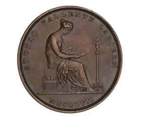 A circular, brown medal depicts a woman in classicized clothing in relief. The woman is surrounded by text in Latin. She is seated and reads by lamplight.