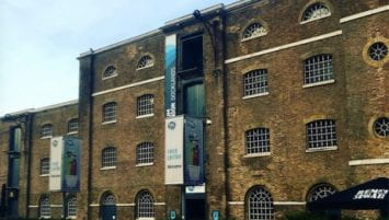 A four story, brown brick warehouse with large windows. Outside the building are signs advertising the Museum of London Docklands.