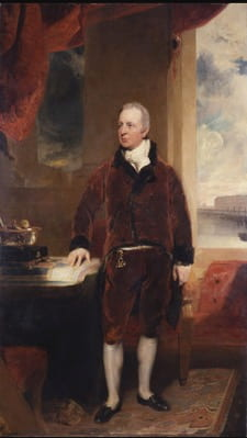 Vertical oil portrait of George Hibbert. Hibbert wears a brown suit and is painted standing with his face turned to the viewer's left. His hand rests atop the architect's plans for the West India Docks on a desk and in the background the West India Quay is visible through an open window.