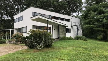 A white modern house with gray trim surrounded by grass and trees.