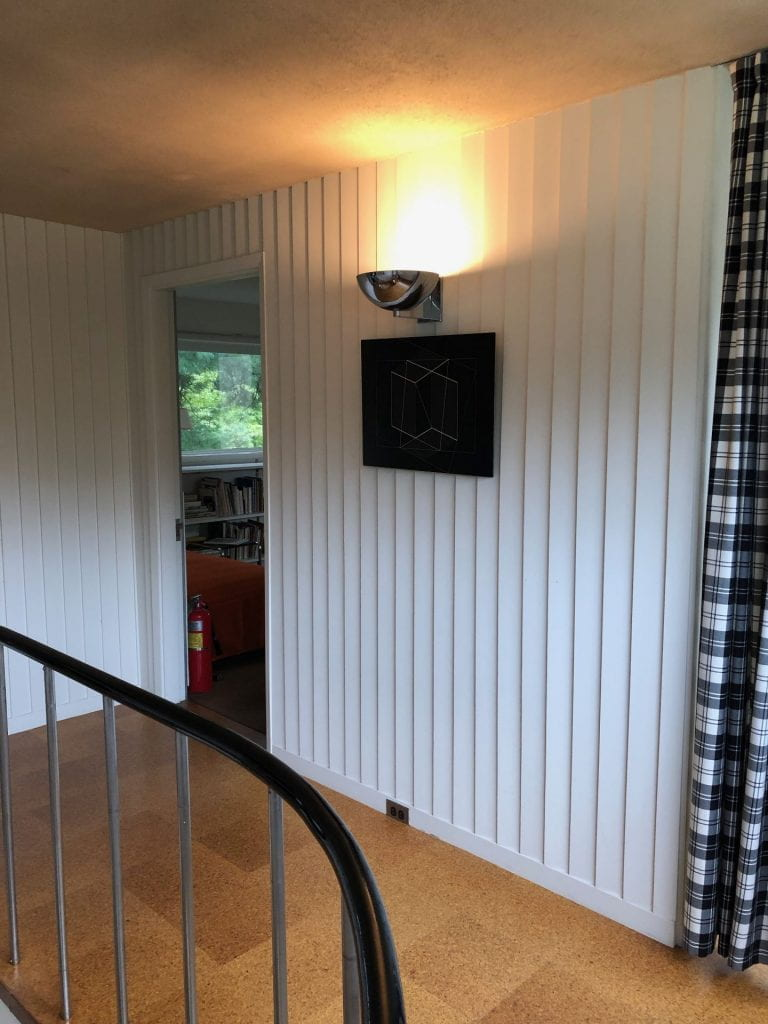 A hallway with vertical clapboards painted white.
