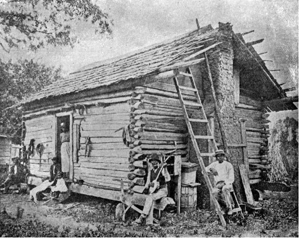 Photograph of a figures around a log-cabin construction.