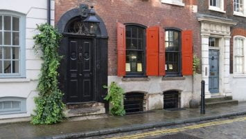 a brick building with a black door and red shutters. Foliage grows on the gutter. A gas lamp burns over the door of the building.