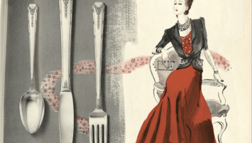 A silverware advertisement in black and white greyscale, accented by red and pink. On one side, there is silverware with a delicate floral pattern. On the other, there is a seated model dressed in a fashionable evening ensemble