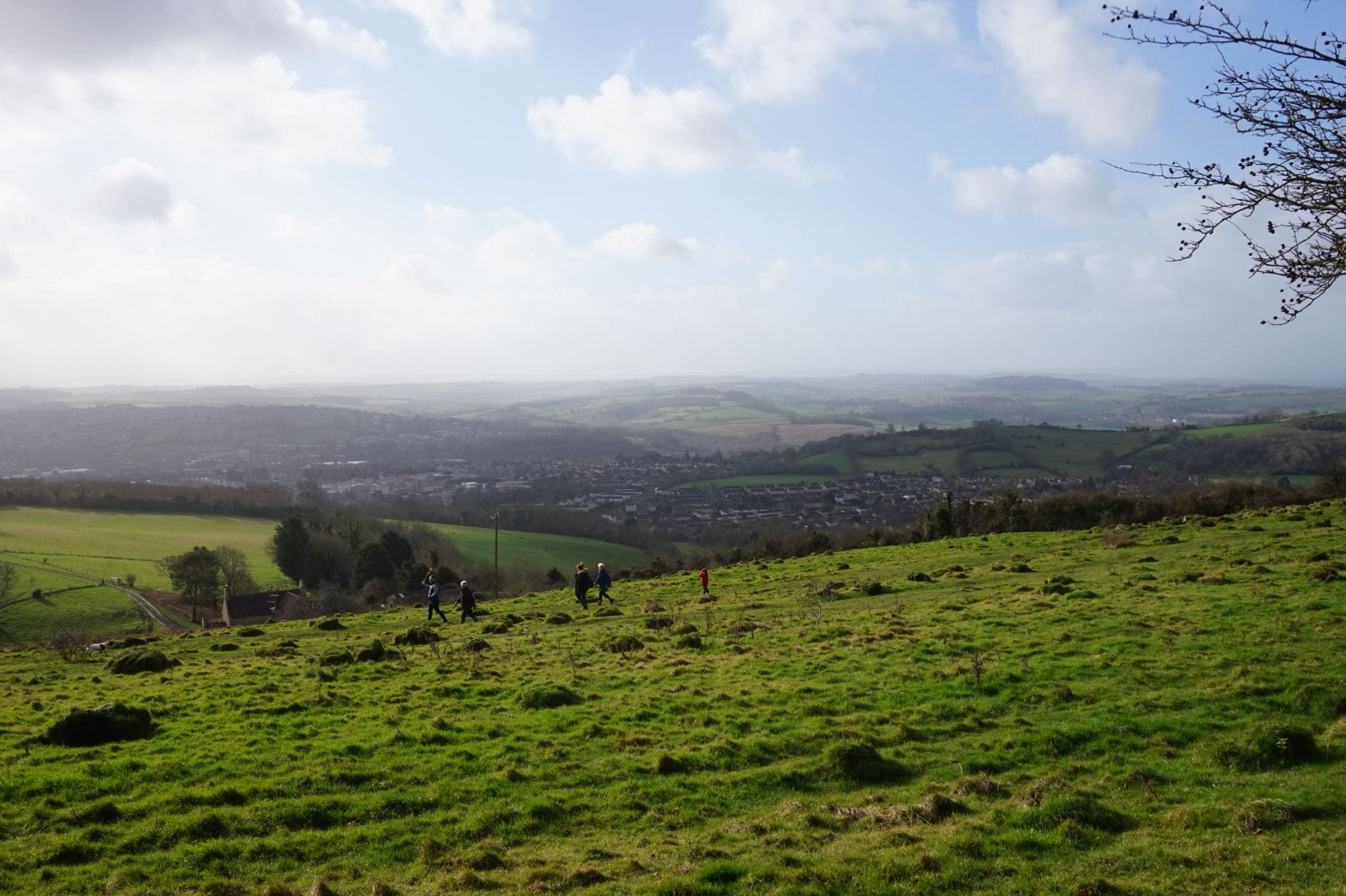 a green landscape of rolling hill with a blue sky dotted with puffy white clouds