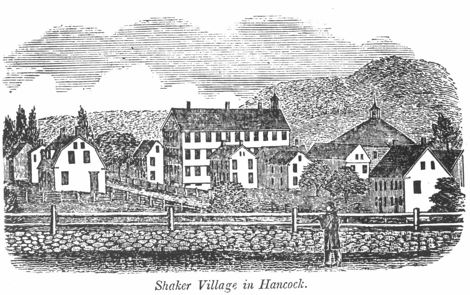 Black and white photograph of a woodcut produced of the Shaker Village at Hancock, Massachusetts. The image shows numerous buildings and trees, all of different size, behind a white picket fence which sits atop a short stone wall. A person wearing a long coat and a large brimmed hat  is standing in front of the fence looking at the village.