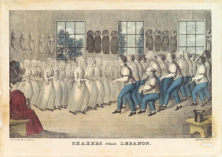 Color-lithograph print showing Shaker men and Shaker women dressed in traditional Shaker costume dancing in the middle of a Shaker meeting house on a wooden floor. Bonnets, hats, and coats are hung up on the wall behind the dancing members. In the foreground, visitors can be seen in nineteenth century dress watching the ritual.