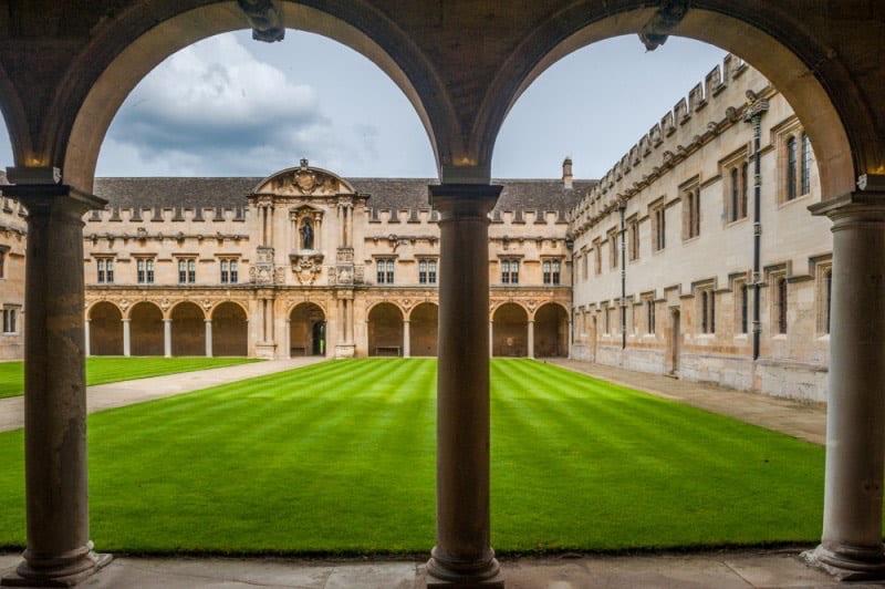 a view of a grassy quad through an arch