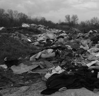A black and white photo of scattered fabrics and clothes next to rubbles of rocks and within the backdrop of trees and shrubs from Juan deGado's Altered Landscapes 2016 exhibition.